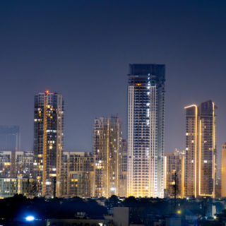High rise multi story skyscrapers lit up at night with small houses in the foreground at night in gurgaon delhi